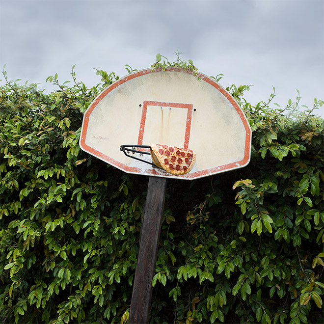 Playing basketball with pizza is an awkward idea.
