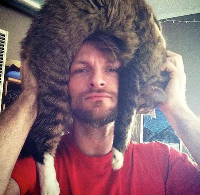 Wearing cat as a hat.