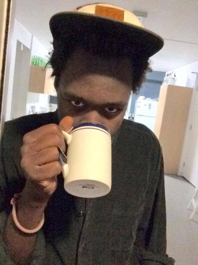 Handsome black man drinking coffee or tea.